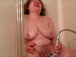 Busty mature white lady in the shower room spraying her pussy