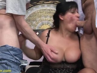 Busty dark-haired lady gets double fucked on a comfy couch
