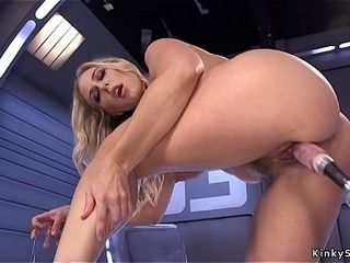 Enormous hooters blond in high high-heeled slippers on machine